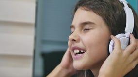 Подросток девушки поя в наушниках музыки школьница слушает к музыке онлайн и танцует и внутри помещения поет акции видеоматериалы