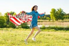 Подросток девушки при американский флаг бежать через луг зеленого цвета лета на заходе солнца Предпосылка природы, сельский ландш Стоковые Изображения RF