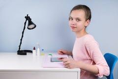 Подросток девушки сидя на таблице получая готовый нести объективы для коррекции зрения Стоковые Изображения