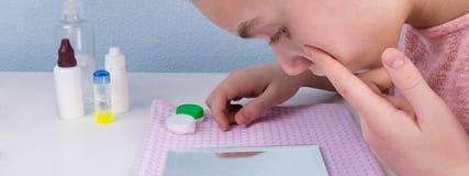 Подросток девушки сидя на таблице смотря глаз в зеркале перед установкой на объективы, концом-вверх Стоковое фото RF