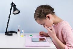 Подросток девушки сидя на таблице смотря глаз в зеркале перед установкой на объективы Стоковые Фотографии RF