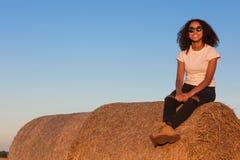 Подросток девушки смешанной гонки Афро-американский сидя на связке сена стоковые фото