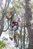 Подросток девушки с взбираясь оборудованием в парке атракционов веревочки Стоковые Изображения