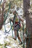 Подросток девушки с взбираясь оборудованием в парке атракционов веревочки Стоковое фото RF