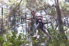 Подросток девушки с взбираясь оборудованием в парке атракционов веревочки Стоковое Изображение RF