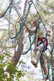 Подросток девушки с взбираясь оборудованием в парке атракционов веревочки Стоковая Фотография RF