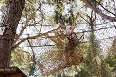 Подросток девушки с взбираясь оборудованием в парке атракционов веревочки Стоковые Изображения RF