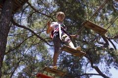 Подросток девушки с взбираясь оборудованием в парке атракционов веревочки Стоковые Фотографии RF