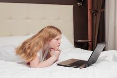 Подросток девушки с компьтер-книжкой в кровати Стоковые Фотографии RF
