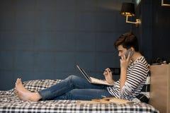 Подросток делая домашнюю работу в кровати Стоковое Фото
