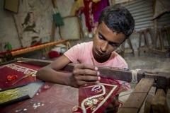 Подросток добавляет деталь к традиционному сари Jamdani в Mirpur Benarashi Palli, Дакке, Бангладеше Стоковое Фото