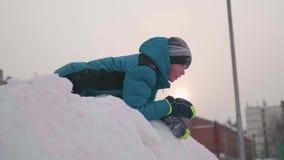 Подросток играя на снежной горе Взгляд от верхней части вниз Солнечный морозный день Потеха и игры в свежем воздухе сток-видео