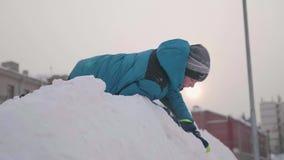 Подросток играя на снежной горе Взгляд от верхней части вниз Солнечный морозный день Потеха и игры в свежем воздухе видеоматериал