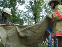 Подросток изучает огонь Лагерь детей лета, команды подростков состязается для скорости стоковая фотография