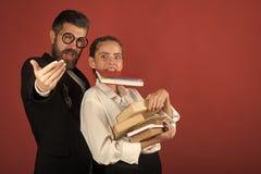 Подросток и гувернер с стеклами держат кучу книг и книги в зубах задняя школа принципиальной схемы к Девушка и бородатый человек  стоковые фотографии rf