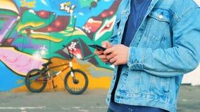 Подросток печатая на телефоне на предпосылке велосипеда, конец вверх видеоматериал