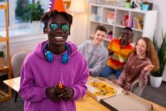 Подросток празднуя день рождения держа меньшую булочку со свечой стоковое изображение rf