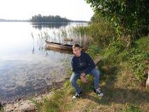 Подросток сидит на речном береге Стоковое фото RF