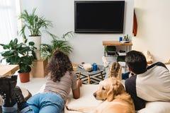 подросток смотря ТВ и лежа на кровати стоковые фотографии rf