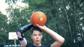 Подросток с простетической рукой бросает баскетбол