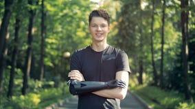 Подросток с футуристической бионической простетической рукой стоит в парке и усмехается на камере