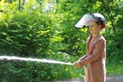Подросток уча профессию пожарного Девушка в шлеме огня льет воду от шланга Стоковое Фото