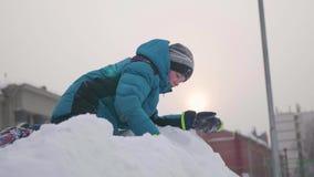 Подросток na górze снежной горы, ходов идет снег и смех Солнечный морозный день Потеха и игры в свежем воздухе акции видеоматериалы