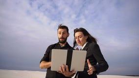 Подруга и парень в командировке используя компьтер-книжку, который нужно связывать с родителями видеоматериал