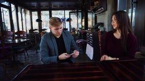 Подруга и парень с smartwatch обсуждая дизайн собственной кофейни и принимая фото используя smartphone акции видеоматериалы