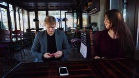 Подруга причиняет ревность парня s путем вызывать друга с smartphone, парнем с smartwatch выбирает вверх чернь видеоматериал