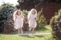 2 подруги бегут через парк весны держа руки Стоковые Фотографии RF