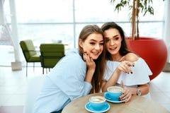 Подруги выпивая кофе в кафе Стоковые Изображения