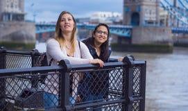 2 подруги в Лондоне - ослабляющ на мосте башни Стоковое Изображение
