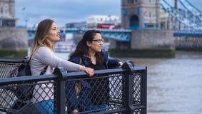 2 подруги в Лондоне - ослабляющ на мосте башни Стоковые Фотографии RF