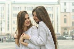 2 подруги держат руки и околпачивают вокруг в городе Стоковые Фотографии RF
