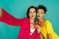 2 подруги дуя поцелуи на предпосылке студии azur Стоковое Фото