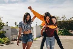 3 подруги играя в улице стоковое изображение