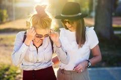 Подруги имея потеху в парке на заходе солнца Стоковые Фотографии RF
