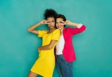 2 подруги околпачивая и танцуя на предпосылке студии azur Стоковое фото RF