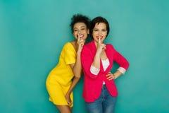 2 подруги показывая символ безмолвия на предпосылке студии azur Стоковая Фотография