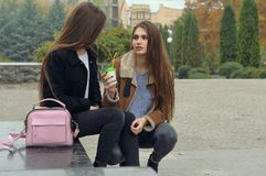 2 подруги пробуют нагревать с горячим питьем в outdoors Стоковое Изображение
