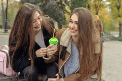 2 подруги пробуют нагревать с горячим питьем в outdoors Стоковая Фотография