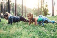 2 подруги разрабатывая outdoors делать тренировку планки на траве Стоковые Изображения RF