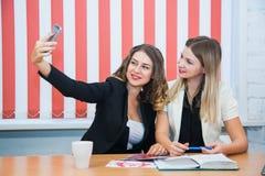 2 подруги сидят совместно беседа обсуждают улыбку делают selfie Стоковое фото RF