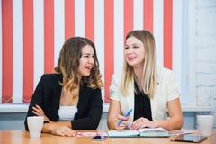 2 подруги сидят совместно беседа обсуждают улыбку Стоковая Фотография RF