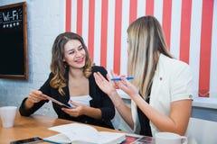 2 подруги сидят совместно беседа обсуждают улыбку Стоковое Изображение