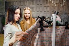 2 подруги смотря одежды в магазине моды женщина ног принципиальной схемы мешка предпосылки ходя по магазинам белая сбывание Стоковое Изображение RF