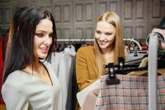 2 подруги смотря одежды в магазине моды женщина ног принципиальной схемы мешка предпосылки ходя по магазинам белая сбывание Стоковые Изображения RF