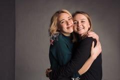 2 подруги стоя совместно, обнимая, смеясь над и усмехаясь Студия снятая в серой стене Стоковые Изображения