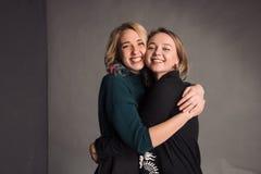 2 подруги стоя совместно, обнимая, смеясь над и усмехаясь Студия снятая в серой стене Стоковые Фото